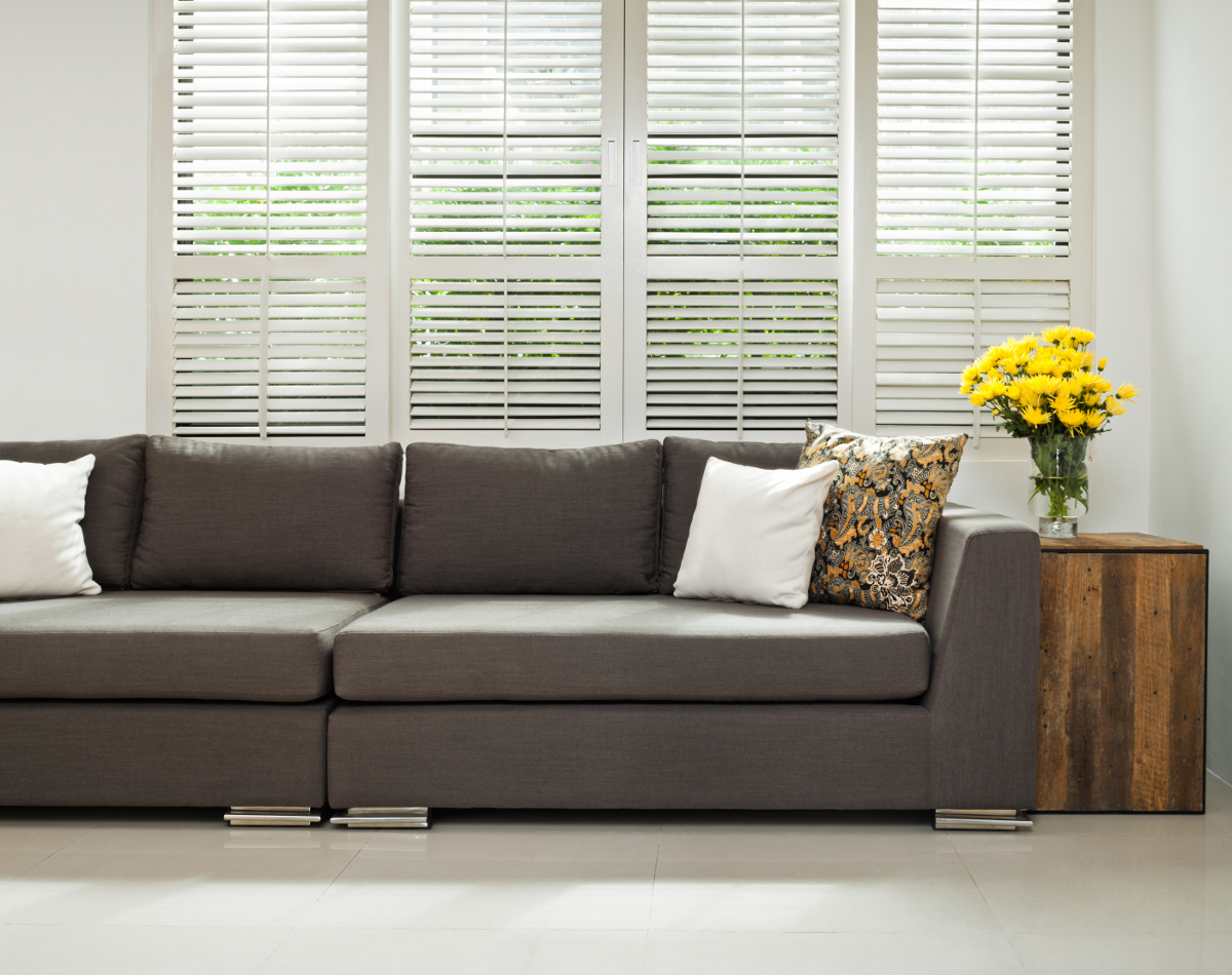 Grey sofa with pillows in front of shuttered windows